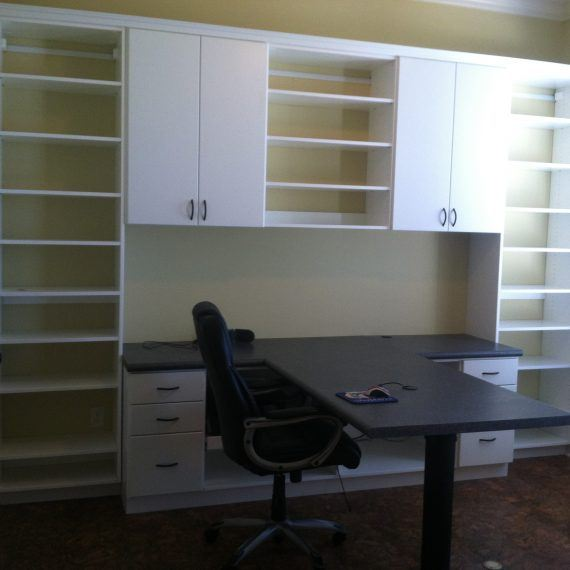 a home office with white cabinets and shelves